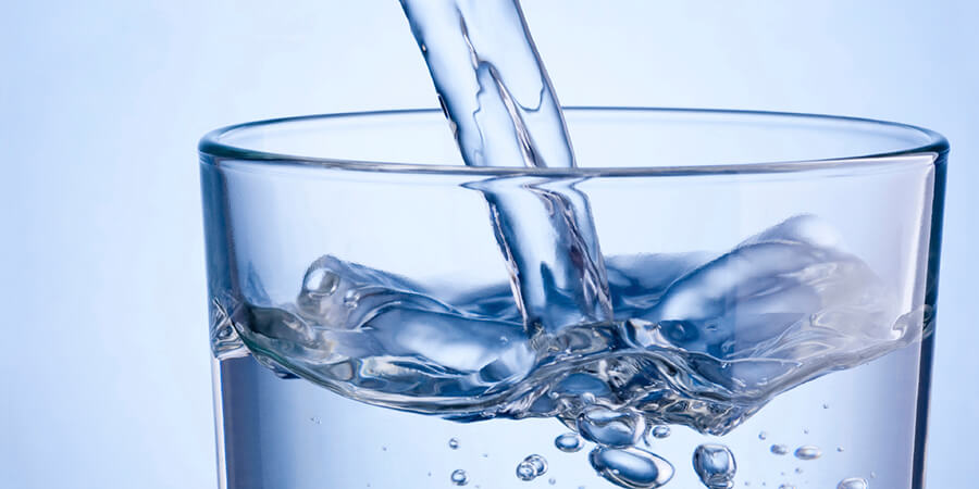 Closeup-pouring-water-into-glass-on-a-blue-background-000045207098_Medium